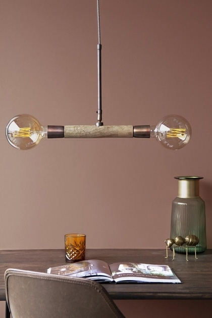 Lifestyle image of twin bulb ceiling light over dining table with open magazine and glassware with mauve coloured wall background