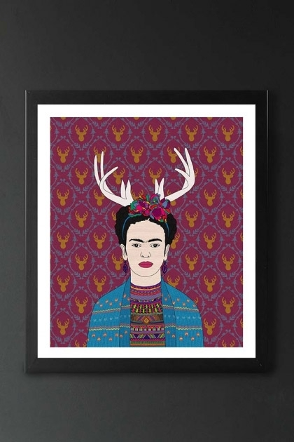 lifestyle image of Unframed Frida Fine Art Print frida khalo with antlers on purple background in black frame on dark wall background