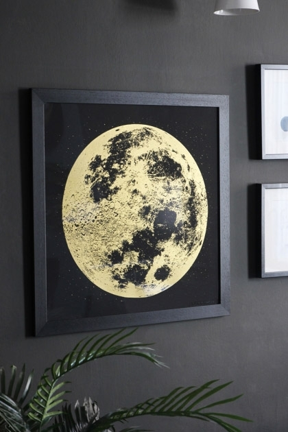 lifestyle image of Unframed Gold Moon Art Print on wall with plant and other prints