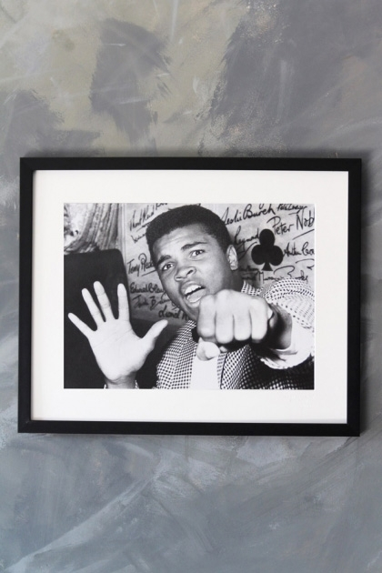 lifestyle image of Unframed Paea Art Print - Mohamed Ali Poing black and white photograph in black frame on distressed grey wall background