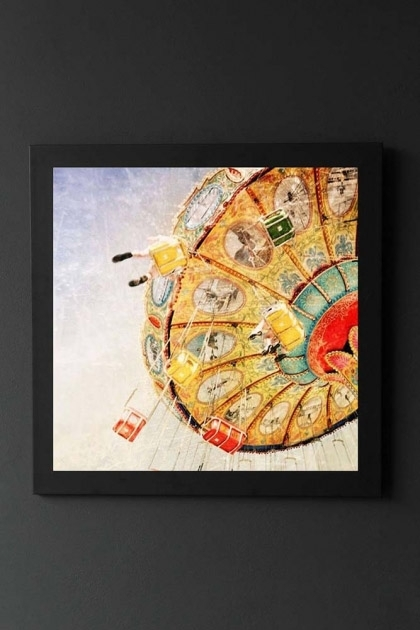lifestyle image of Unframed Sea Swings Fine Art Print fairground ride in black frame on dark wall background