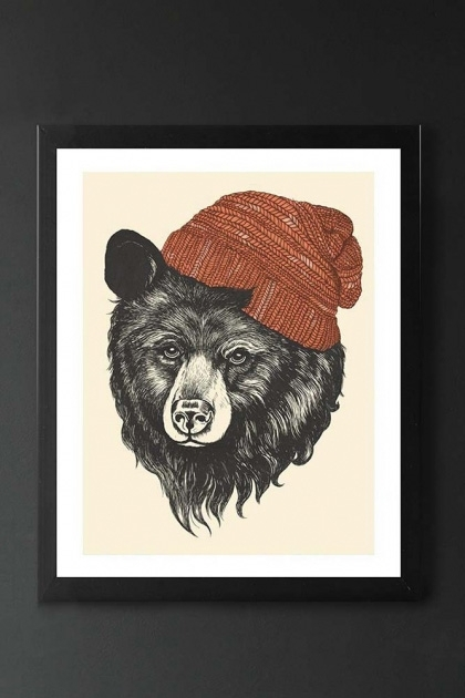 lifestyle image of Unframed Zissou the Bear Fine Art Print grey bear with orange beanie in black frame on dark wall background