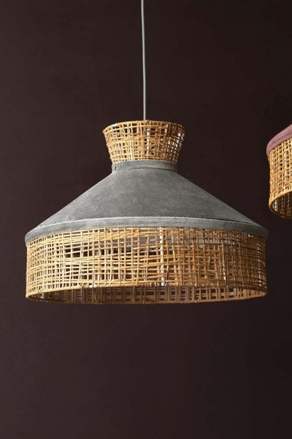 Lifestyle image of the Silver Grey Velvet & Rattan Pendant Ceiling Light on a dark brown wall background