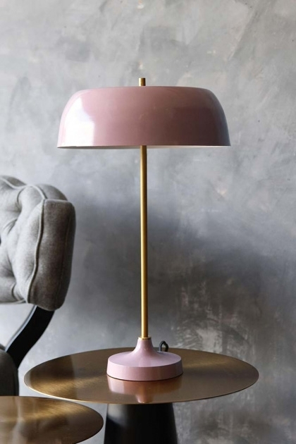 lifestyle image of Ventura Table Lamp - Pink on gold side table with grey cloud chair and distressed grey wall background
