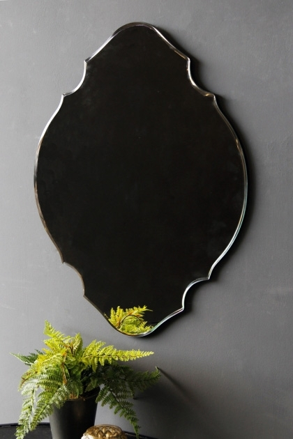 lifestyle image of Vintage Style Art Deco Mirror with plant on grey wall background