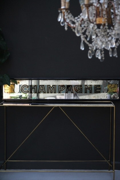 lifestyle image of Vintage Style Champagne Mirror on console table with chandelier and dark wall background