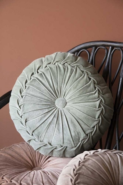 Lifestyle image of the Vintage Style Velvet Rouched Round Cushion in Mint Green on black rattan chair with other cushions and emanuella painted wall background