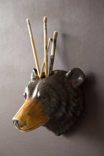 Lifestyle image of the Wall Hung Beautiful Bear Vase/Container hung on a wall with paintbrushes inside on dark wall background