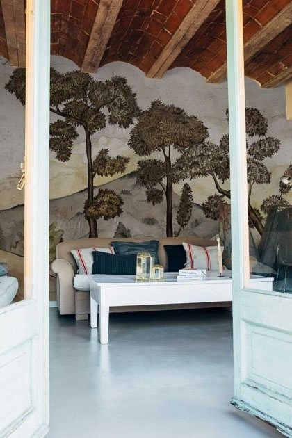 Lifestyle image of the Watercolour Landscape Wallpaper Mural - Taklamakan Chia Seed through white wooden open doors and with white coffee table and sofa and wooden beam ceiling