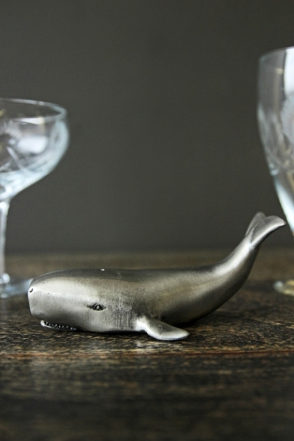 lifestyle image of Whale Bottle Opener with glasses on wooden table and dark wall background