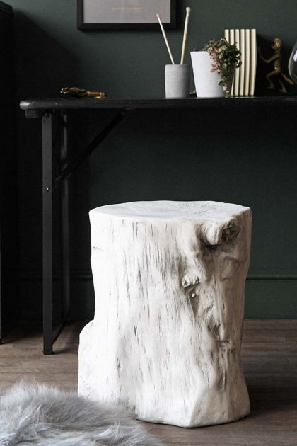 lifestyle image of White Tree Trunk Effect Stand  Side Table on grey sheepskin rug with black desk in background and dark green wall background