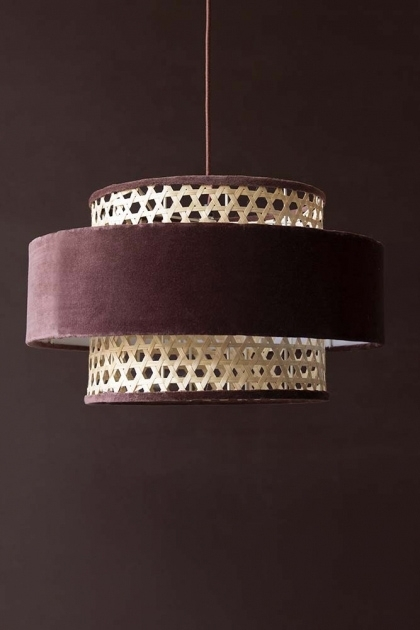 Lifestyle image of the Burgundy Woven Cane & Velvet Cylinder Pendant Ceiling Light with a dark brown wall background