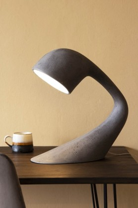 Lifestyle image of the 100% Recycled Unique Large Arched Table Light - Concrete Grey on black side table with terracotta mug and cloisters painted wall background