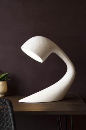 Lifestyle image of the 100% Recycled Unique Large Arched Table Light - Stone White on black side table with small plant and dark wall background