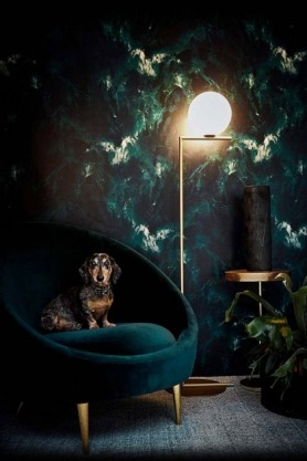 lifestyle image of 17 Patterns Beyond Nebulous Wallpaper - Green/Blue with teal velvet armchair with sausage dog sitting on it and lit up floor lamp