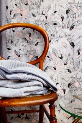 lifestyle image of 17 Patterns Flamingo Wallpaper - 4 Colours Available with wooden chair and folded grey blanket