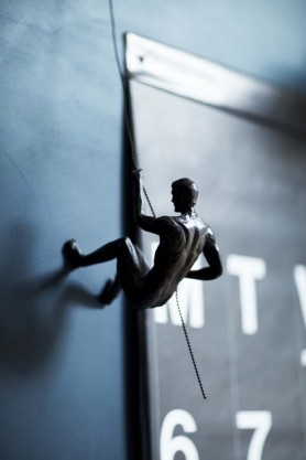lifestyle image of Abseiling Man next to wall calendar hung on dark wall background