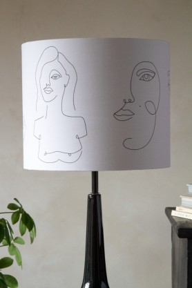 Lifestyle image of the Linea Face Design Pendant & Lamp Shade - White With Gold Interior on a lamp