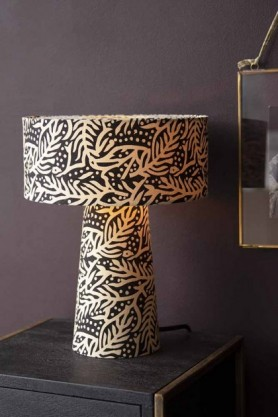 Lifestyle image of the All Over Black & Natural Printed Table Lamp illuminated on black bedside table with dark wall background