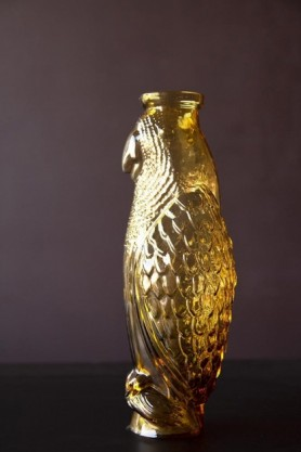 Lifestyle image of the Amber Glass Cockatoo Carafe on black surface and dark wall background
