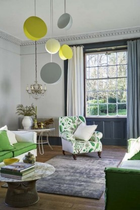 lifestyle image of Amour Rug - Steel 02 - 3 Sizes Available with green patterned armchair, green and white ceiling lights and bay window in background