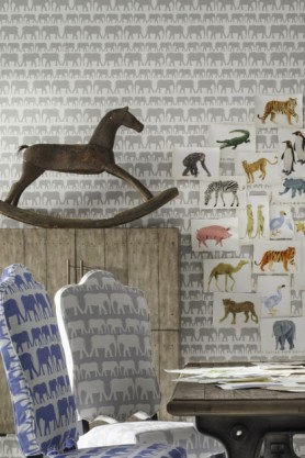 lifestyle image of Andrew Martin Nell Wallpaper - 3 Colours Available with patterned chairs and rocking horse on wooden side board