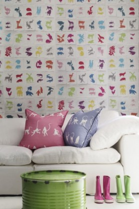 lifestyle image of Two By Two Wallpaper By Andrew Martin with white sofa and pink and purple cushions behind green pouffe and coloured wellington boots