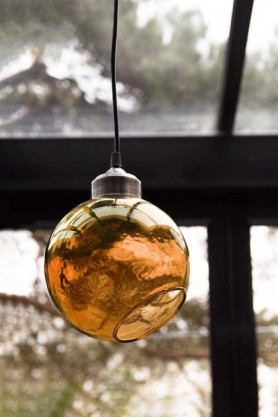 Lifestyle of angled glass sphere pendant ceiling light in amber with windows background