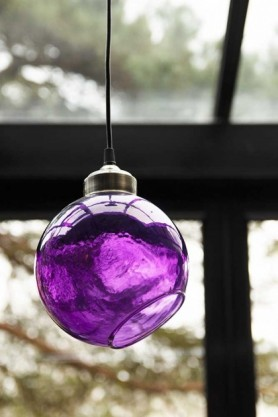 Lifestyle of angled glass sphere pendant ceiling light in plum with window background