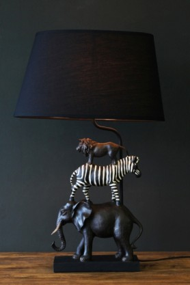 lifestyle image of Animal Safari Table Lamp on wooden table and dark wall background