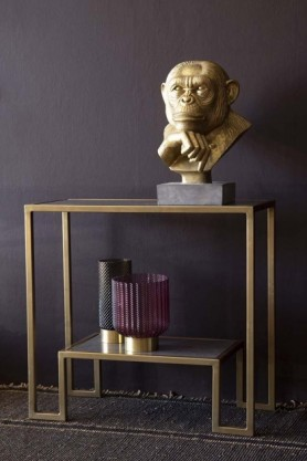lifestyle image of Antique Brass & Marble Two-Tier Shelf Unit with gold monkey bust and glass vases on dark patterned rug flooring and dark wall background