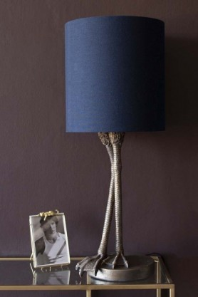 lifestyle image of Antique Bronze Flamingo Leg Table Lamp With Navy Blue Shade with Leopard Picture Frame on gold and glass console table and dark wall background