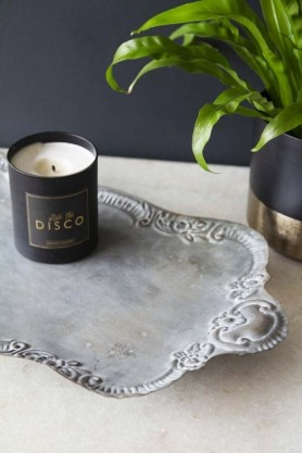 lifestyle image of Antique Grey Victorian-Style Tray with candle on tray and plant in background on pale surface and dark wall background
