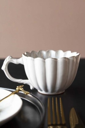 lifestyle image of Antique White Chateau Mug with tableware in foreground on black table and pale wall background