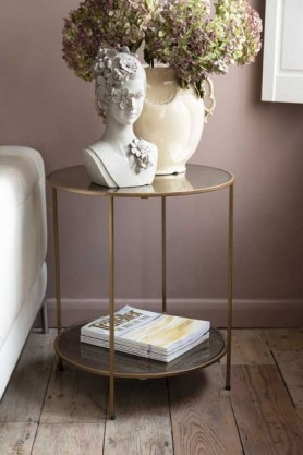 lifestyle image of Antiqued Mirror Side Table next to grey sofa with white bust and vase with flowers in on top and wooden flooring and purple wall background