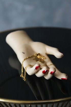 lifestyle image of Antiqued Relaxed Hand Jewellery Holder with gold necklace inside on black table with blue wall background