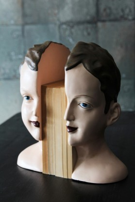 lifestyle image of Antiqued Split Deco Head Bookends with books in between on black table with grey tile wallpaper background