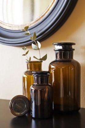 Lifestyle image of all 3 sizes available of the Apothecary Style Brown Glass Storage Bottle in a display on black surface and round mirror on pale wall background