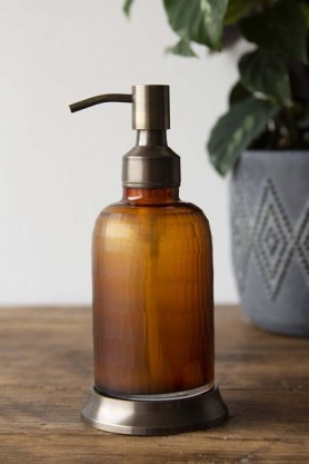lifestyle image of Apothecary Style Soap & Lotion Dispenser with plant in vase on wooden table and pale wall background