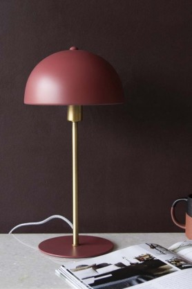 Lifestyle image of the Art Deco Canopy Table Lamp - Berry Red on marble table with book open and dark wall background