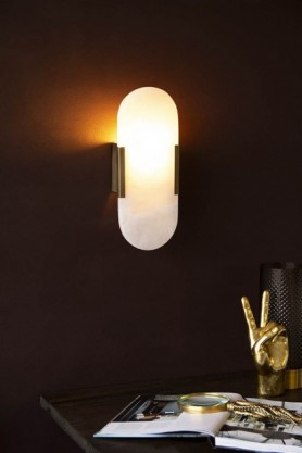 Lifestyle image of Art Deco Oval Marble Wall Light switched on over a desk with open book and Gold Peace Hand Ornament with dark wall background