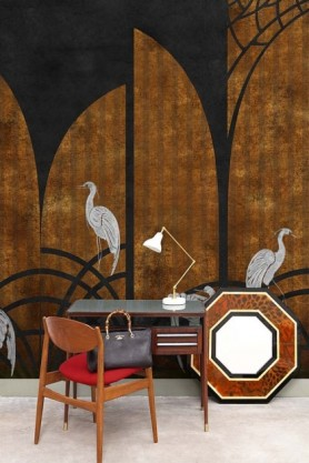 Lifestyle image of the Art Deco Wallpaper Mural - Tassel Ginger with desk and table lamp and red wooden chair with handbag on it and mirror on the floor leaning on wall