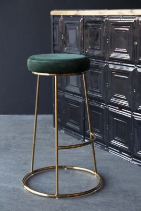 Lifestyle image of the Atlantis Velvet Bar Stool in Rich Green with tin tile bar in background on grey flooring and dark wall background