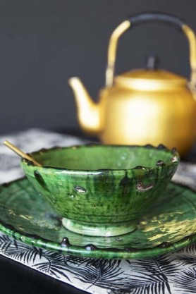 lifestyle image of Authentic Tamegroute Large Bowl - 14cm with gold teapot and black table runner with grey wall background