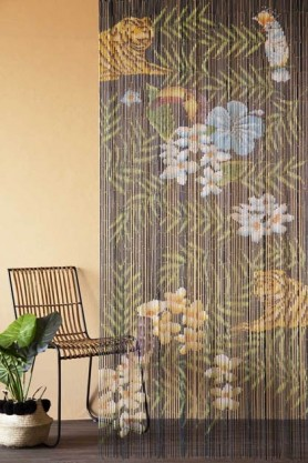 Lifestyle image of the Tropical Design Bamboo Door Curtain on cloisters painted wall with rattan chair and house plant