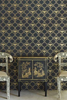 detail image of Barneby Gates Honey Bees Wallpaper - Gold on Charcoal with black and gold cabinet and two chairs