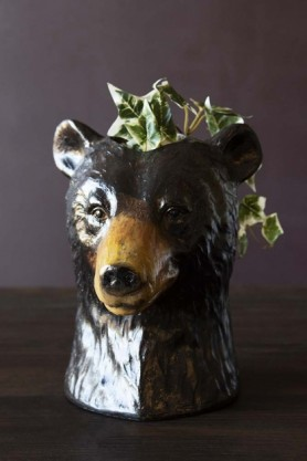 Lifestyle image of the Beautiful Bear Vase with some trailing ivy in it on dark wooden surface and dark wall background