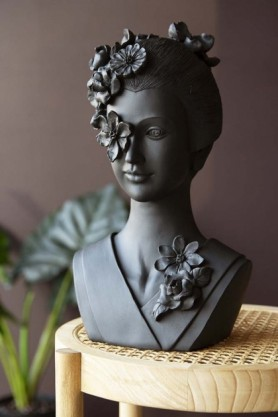 Lifestyle image of the Beautiful Black Geisha Bust With Floral Headdress on pale wooden coffee table with plant in background and dark wall background