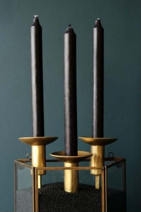 Beautiful black dinner candles in a golden candle holder planted in black sand - Rockett St George lifestyle image