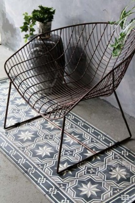 lifestyle image of Beija Vinyl Floor Runner - Gothic Antique on floor with brown wired chair and black vase with plant in on top with grey wall background